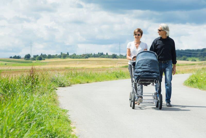Grands-parents faisant une promenade avec la poussette de bébé images libres de droits