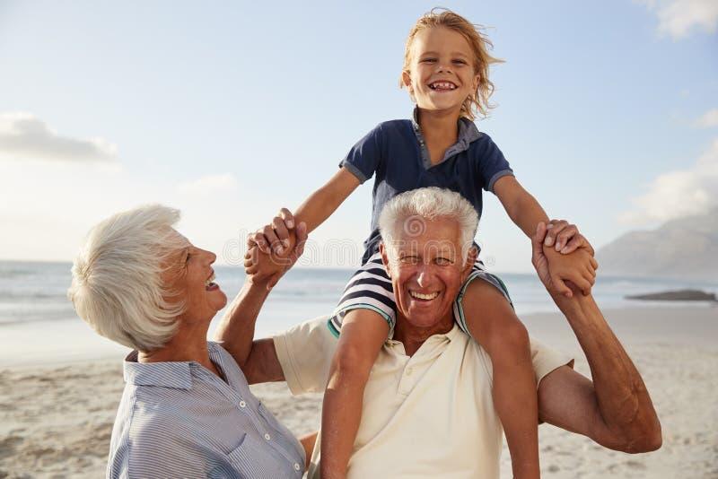 Grands-parents portant le petit-fils sur des épaules sur la promenade le long de la plage images libres de droits
