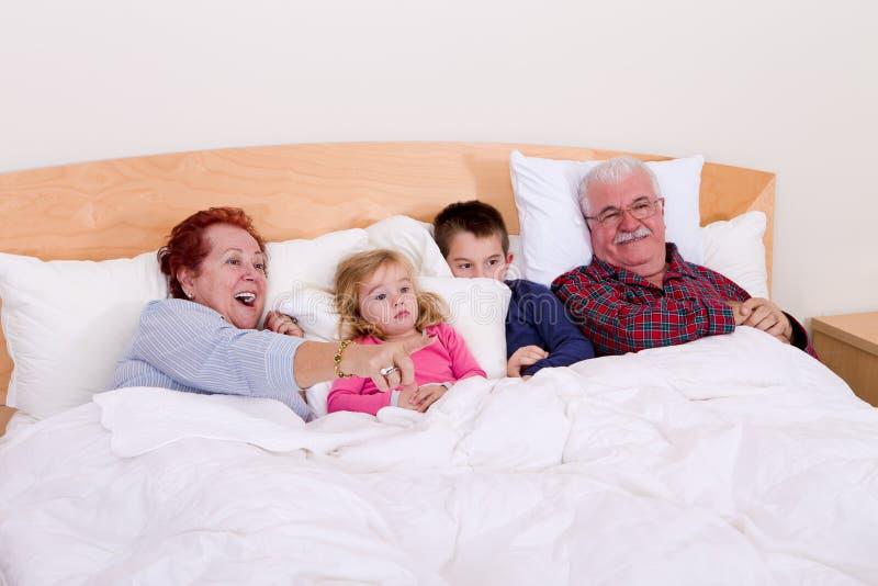 Grands-parents regardant la TV dans le lit avec leurs enfants grands photo stock