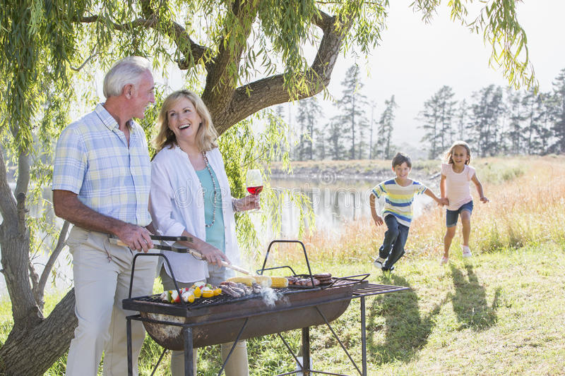 Grands-parents servant des petits-enfants au barbecue de famille photos stock