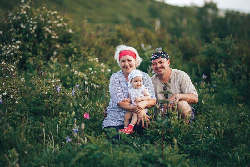 Grands-parents tenant la séance de petite-fille en nature de parc photos stock