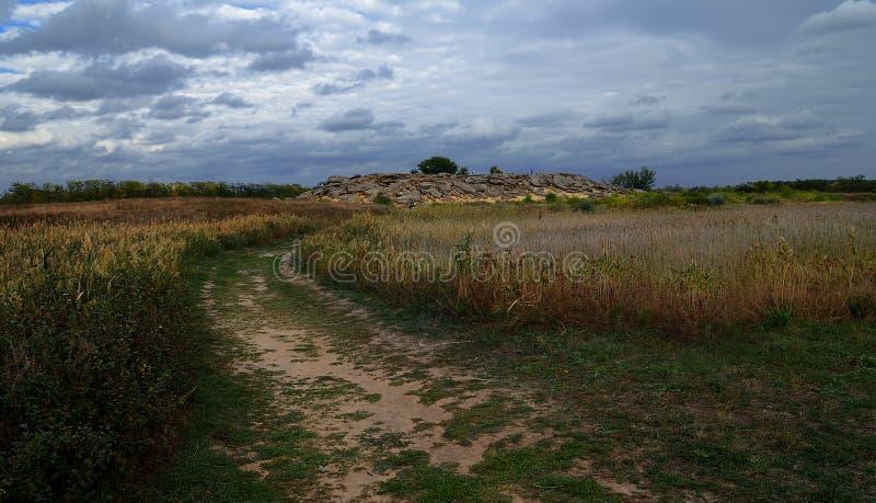 Grands rochers dans le mensonge de Barrens sur le sable parmi le ciel bleu-foncé avant la pluie d'été image libre de droits