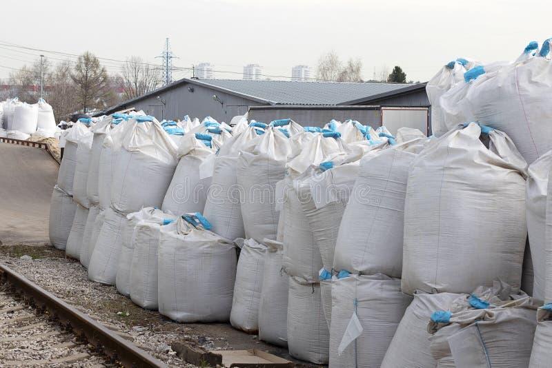 Grands sacs blancs avec le ruban bleu ? l'int?rieur du mensonge de sel sur la rue Des engrais industriels sont stock?s dans les s photos libres de droits