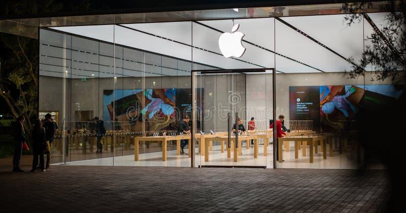 Grands vitraux d'Apple Store aux personnes modernes de bâtiment de nuit travaillant au logo d'Apple d'ordinateurs photo stock