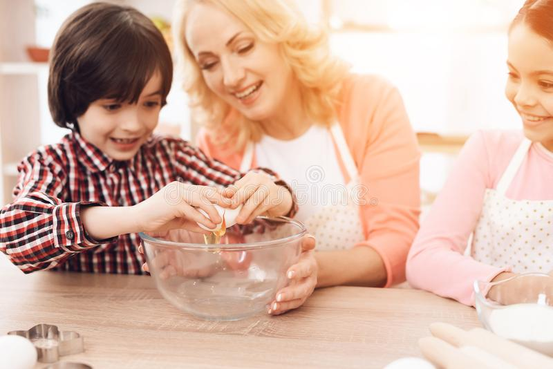 Grandson breaks egg into bowl, sitting next to grandmother and sister sitting behind laptop. stock photos