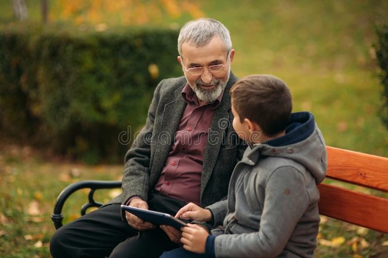 Grandson explains his grandfather how to use tablet. Child help older generation stock photos