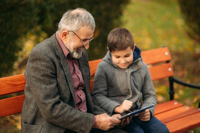 Grandson explains his grandfather how to use tablet. Child help older generation royalty free stock photos