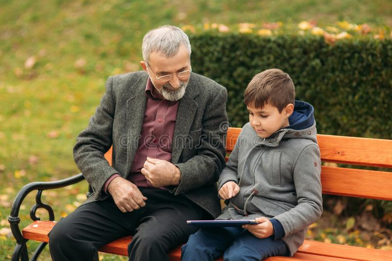 Grandson explains his grandfather how to use tablet. Child help older generation royalty free stock photography