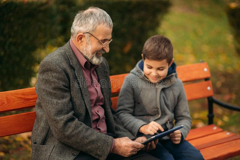 Grandson explains his grandfather how to use tablet. Child help older generation stock images