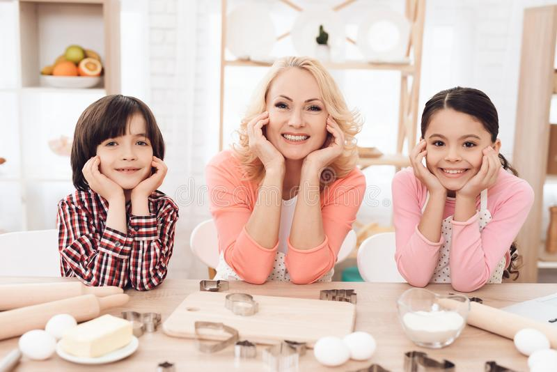 Grandson and granddaughter together with happy grandmother are engaged in cooking in kitchen. royalty free stock images