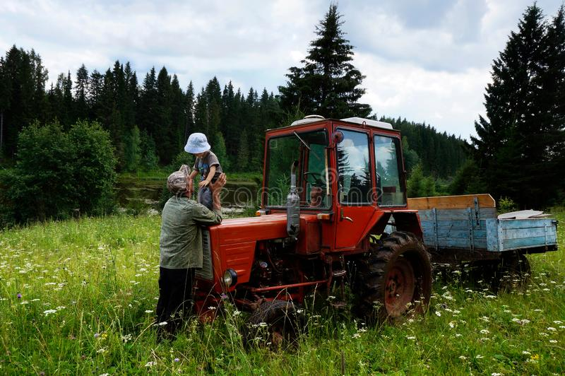 Grandson of with grandfather farmer and a tractor in the forest on meadow royalty free stock images