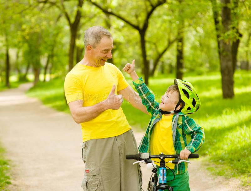 Grandson and grandfather having fun riding a bike stock images
