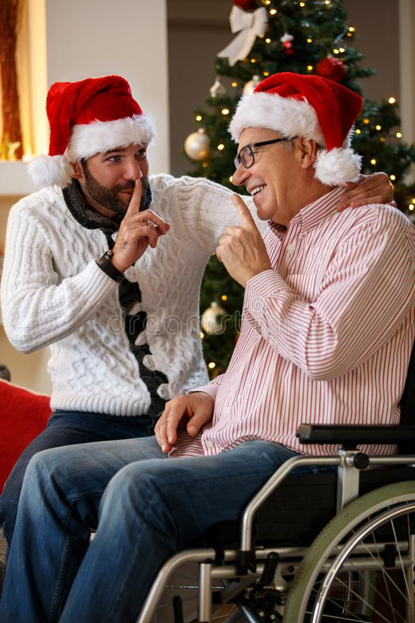 Grandson and grandfather talking secrets on Christmas royalty free stock photos
