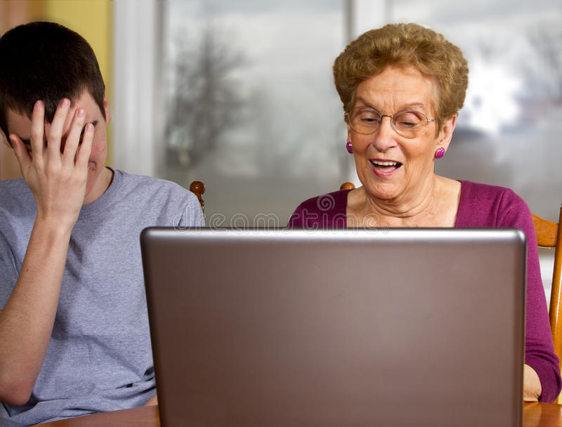 Grandson and grandmother at a laptop. Teen boy frustrated trying to teach grandmother to use a laptop stock photo