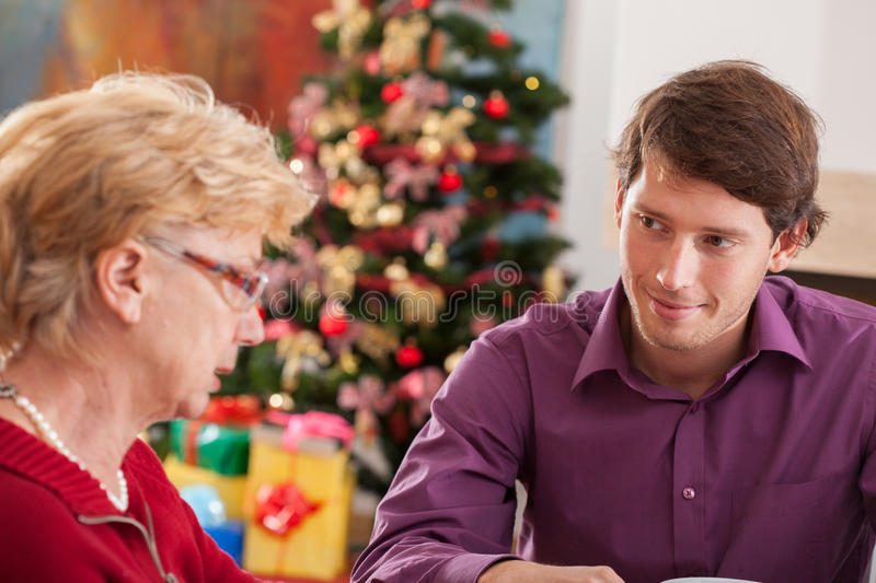 Grandson and grandmother talking. During Christmas dinner stock photo
