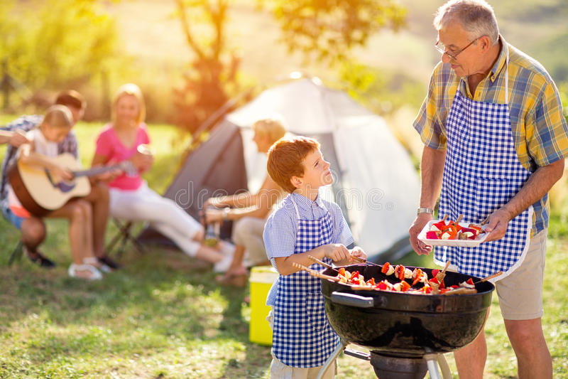 Grandson grilling barbecue with grandfather stock photography