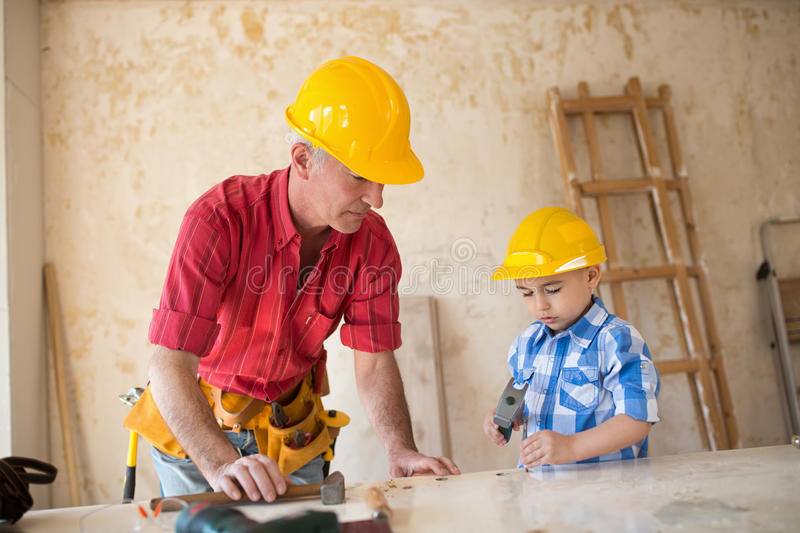 Grandson is helping grandfather in a carpenter`s workshop royalty free stock images