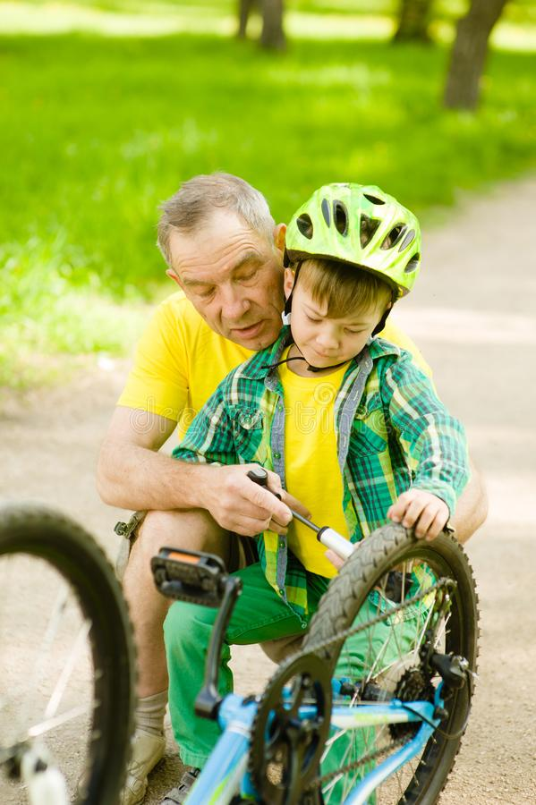 Grandson with his grandfather pumped wheel bicycle stock image