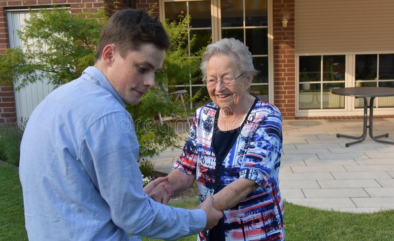 Grandson helps his great-grandma to go. Grandson and his great-grandmother.The boy gently helps his grandma to walk across the lawn royalty free stock images