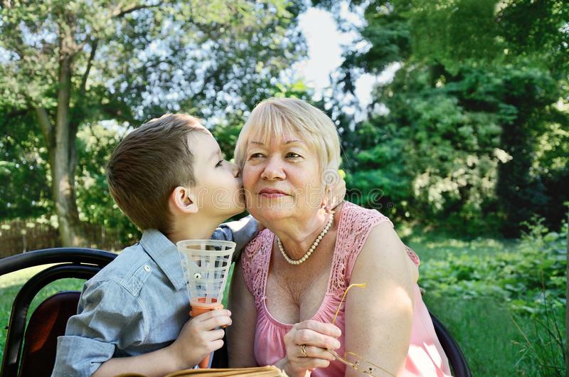 Grandson hugs and kisses on the cheek his grandmother. tears in royalty free stock images