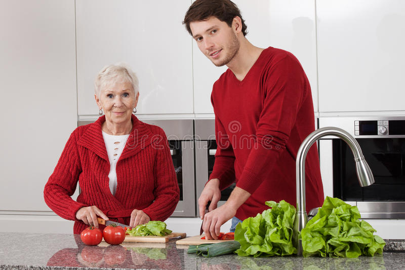 Grandson's help. Young men is helping grandma to prepare lunch stock image