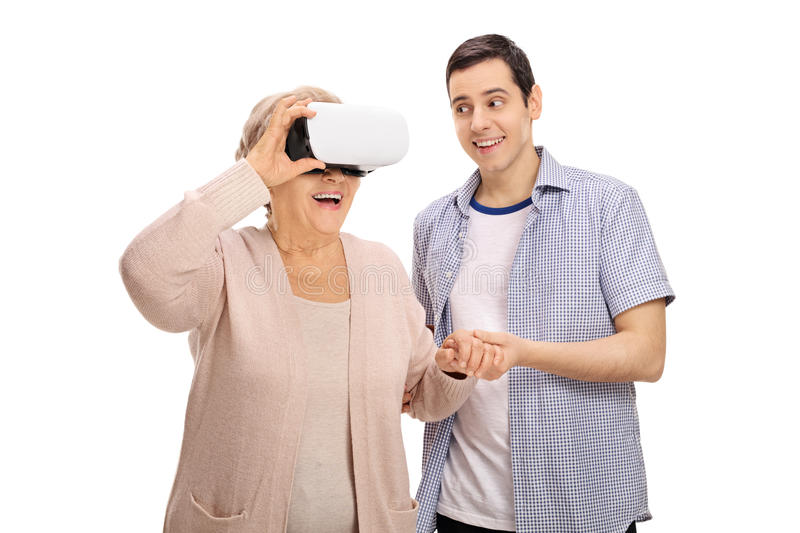 Grandson showing grandmother how to use a VR headset. Grandson showing his grandmother how to use a VR headset isolated on white background royalty free stock photo