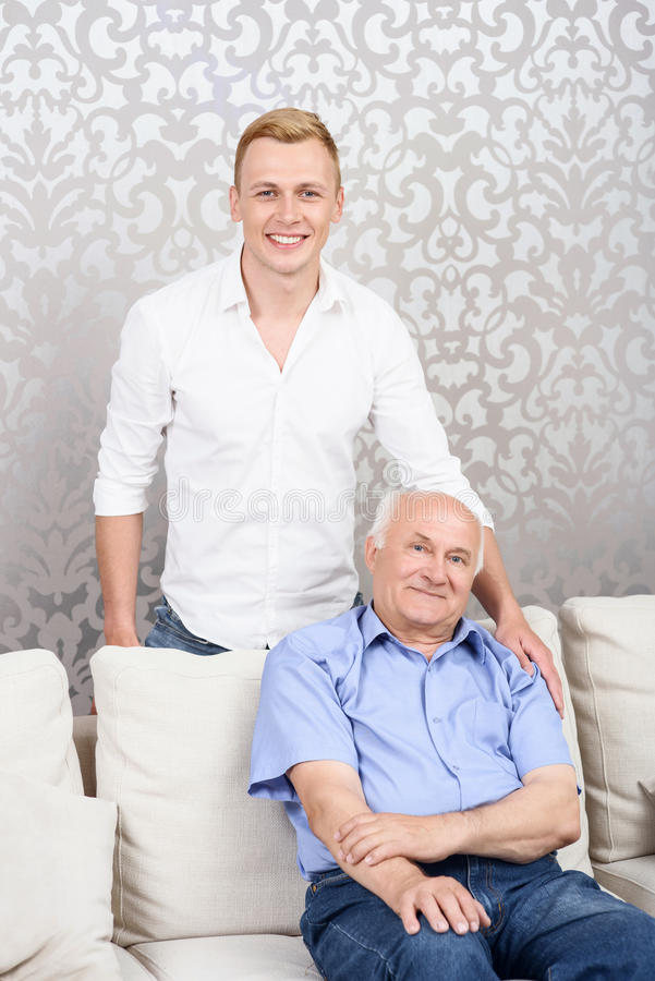 Grandson standing behind his grandfather stock photos