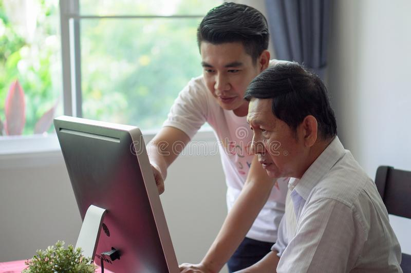 Grandson teaching grandfather how to Using computer and technology in home . young Teacher help senior Man learning to connect stock photo