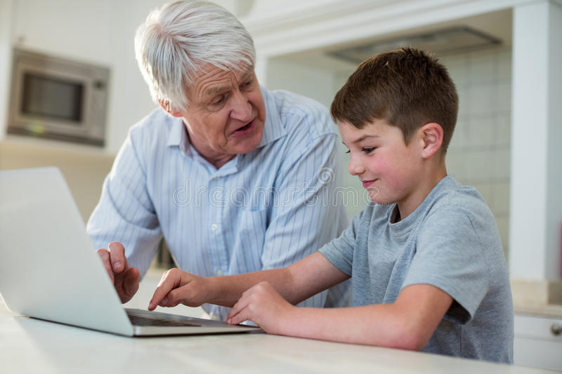 Grandson using laptop with grandfather stock photos