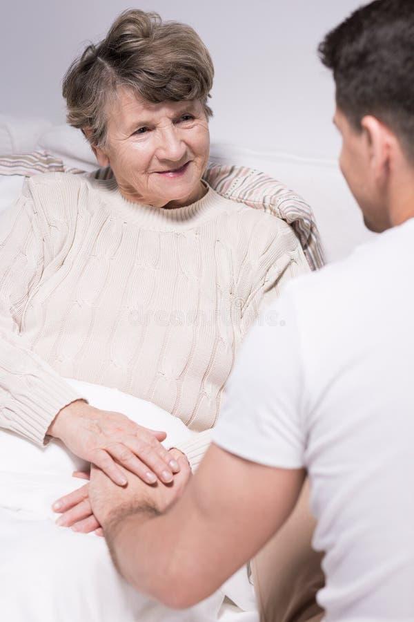 Grandson visiting grandmother at hospital. Photo of grandson visiting his sick grandmother at hospital royalty free stock images
