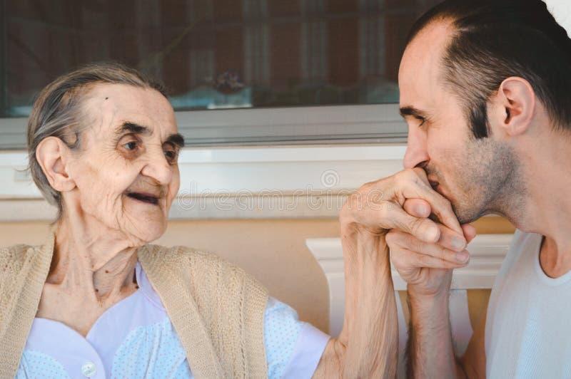 Grandsond χέρι του grandma φιλήματός του, που παρουσιάζει το σεβασμό και αγάπη του στοκ εικόνες
