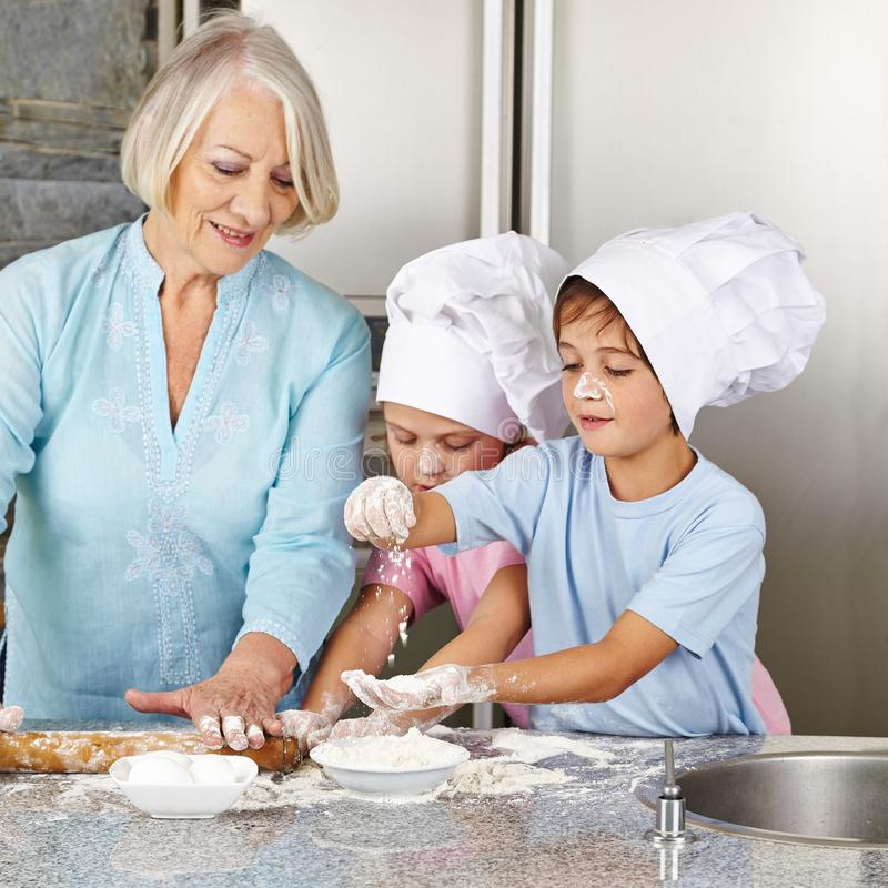 Grandsons help grandma to bake at Christmas. Two grandchildren help grandma to cook biscuits for Christmas in the kitchen stock images