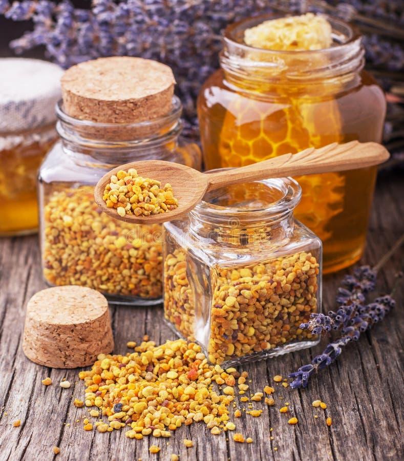 Granelli e propoli del polline dell'ape in mestolo di legno fotografia stock libera da diritti