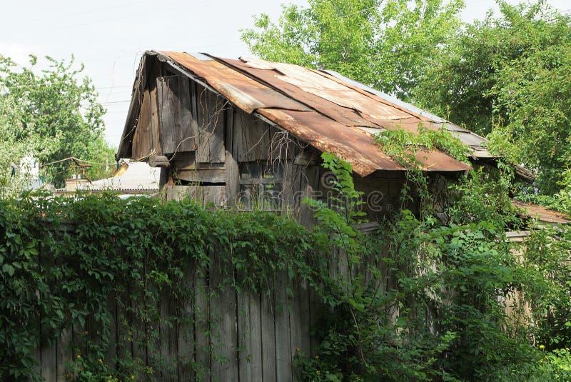 granero abandonado gris con un tejado oxidado detrás de una cerca demasiado grande para su edad con la vegetación verde imagen de archivo