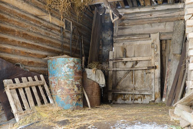 Granero abandonado viejo con los barriles del metal imagen de archivo libre de regalías