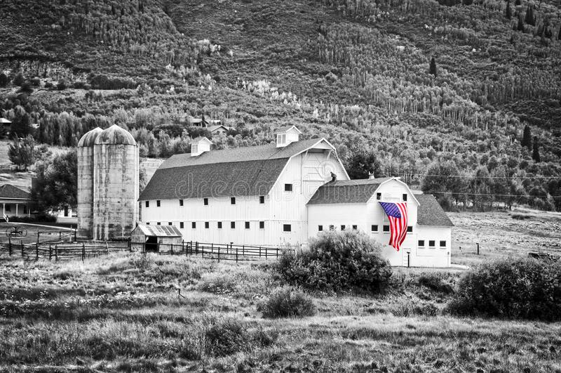 Granero americano del vintage típico con la bandera americana, Park City, Utah - fotografía blanco y negro, color selectivo fotos de archivo libres de regalías
