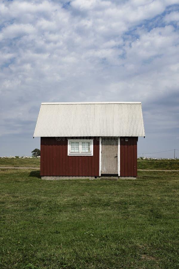 Granero rojo de madera con un tejado blanco en un campo verde grande con el cielo azul nublado fotos de archivo