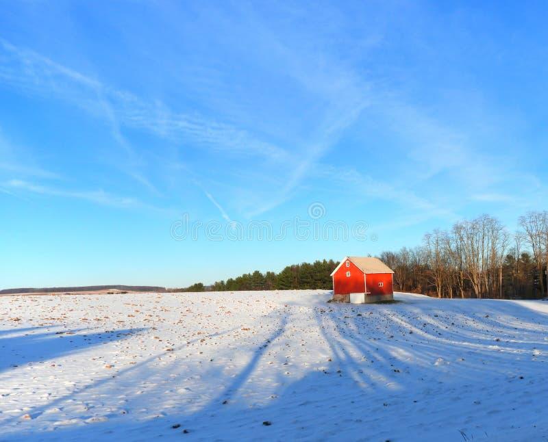 Granero rojo en la colina nevosa del invierno debajo de un cielo azul imagenes de archivo