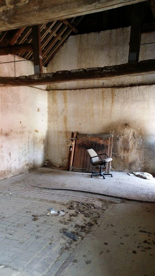 Granero viejo con la puerta de granero y una silla imagen de archivo