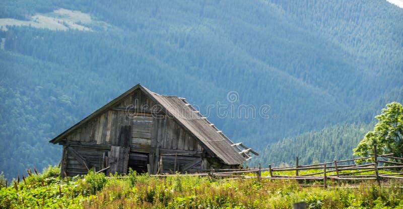 Granero viejo en montañas imagenes de archivo