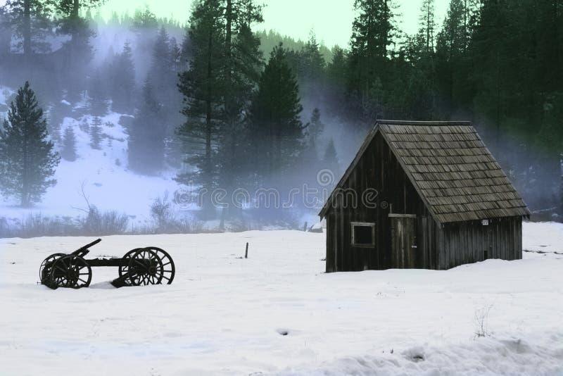 Granero y carro de madera viejo en la nieve imagen de archivo libre de regalías