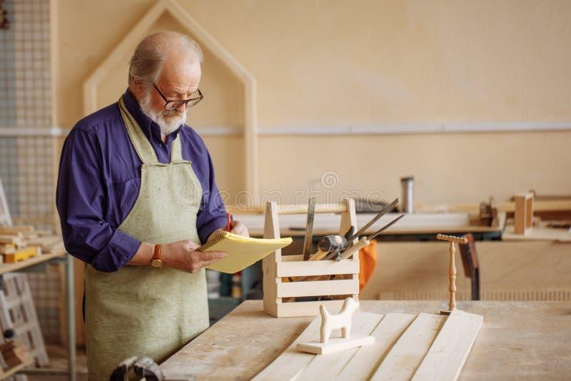 Granfather die omhoog van hout voor zijn kleinzonen en kleindochters huidig maken royalty-vrije stock foto's