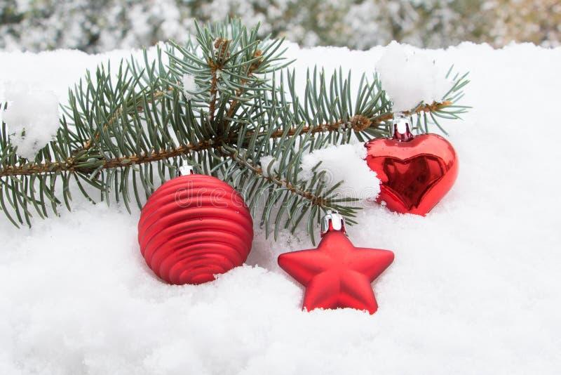 Granfilial med julleksaker i snön royaltyfri foto