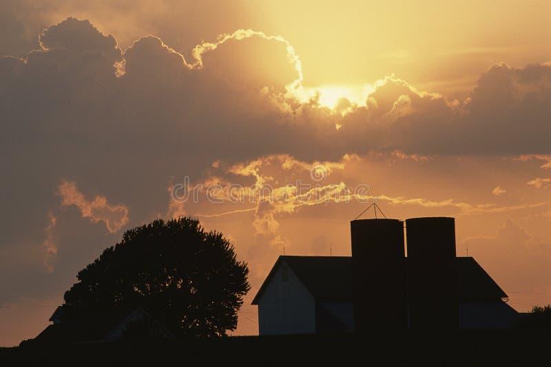 Grange avec le silo au coucher du soleil images stock