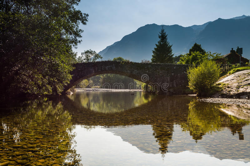 Grange Bridge reflected. Grange Bridge at the village of Grange over the River Derwent in the Lake District royalty free stock images