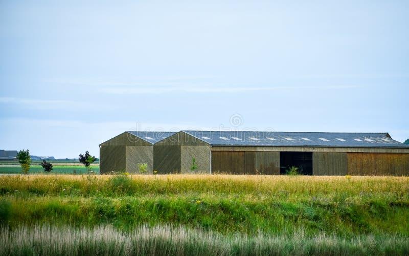 Grange ou entrepôt entre les prés, et les terres cultivables Ciel bleu pour le texte image stock