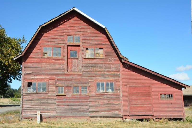 Grange rouge avec les fenêtres cassées et le ciel bleu, vallée de Willamette, Orégon photographie stock libre de droits