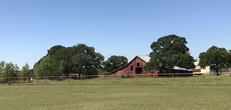 Grange rouge rustique dans la terre de ferme photographie stock