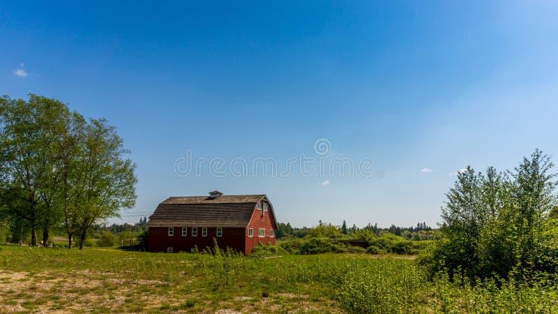 Grange rouge sous les cieux clairs de Bue photos libres de droits