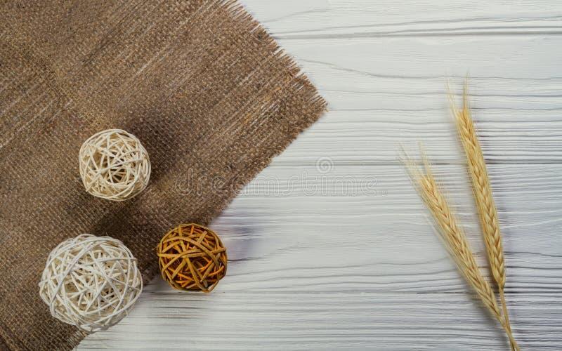 Grani del grano e sfere di legno decorative su fondo di legno bianco fotografie stock